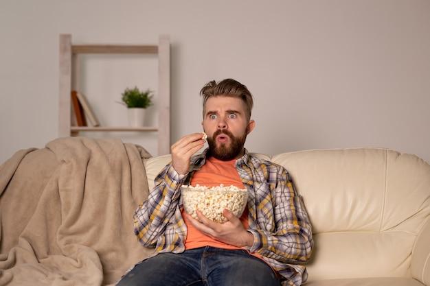 Homem barbudo assistindo filme ou jogos de esporte tv comendo pipoca em casa à noite. cinema, campeonato Foto Premium