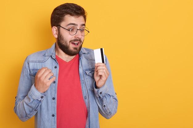 Homem barbudo atônito veste jaqueta jeans, camisa vermelha e óculos, segurando o cartão de crédito nas mãos e parece um cartão de ar com a boca aberta Foto gratuita