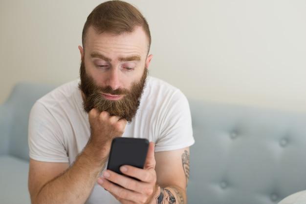 Homem barbudo bonito chato usando smartphone na sala de estar Foto gratuita