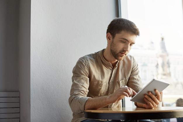 Homem barbudo bonito com cabelo curto em roupas casuais, sentado no café, olhando através de detalhes do projeto de inicialização no tablet. conceito de negócios. Foto gratuita