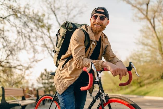 Homem barbudo bonito estilo hippie com jaqueta e óculos escuros andando sozinho com a mochila na bicicleta mochileiro viajante estilo de vida ativo saudável Foto gratuita