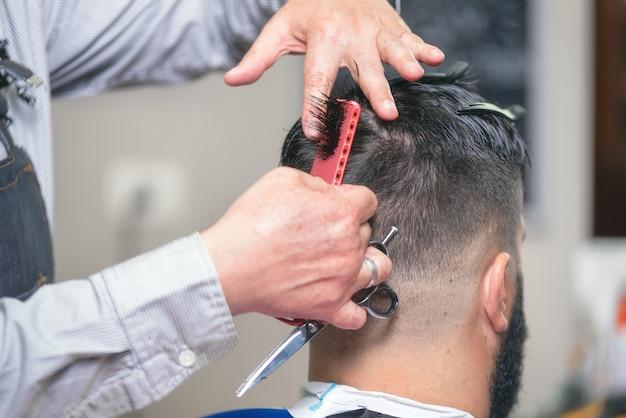 Homem barbudo bonito, tendo o cabelo cortado por uma tesoura na barbearia. Foto Premium