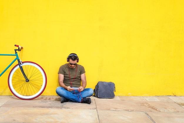 Homem barbudo bonito usando um telefone celular enquanto ouve música em fones de ouvido, gastando tempo com prazer enquanto está sentado perto da bicicleta, ao ar livre Foto Premium