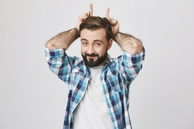 Homem barbudo brincalhão e engraçado fazendo gesto de chifres Foto gratuita