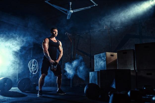 Homem barbudo caucasiano atraente muscular levantando dois kettlebells em um ginásio. placas de peso, halteres e pneus em segundo plano. Foto Premium