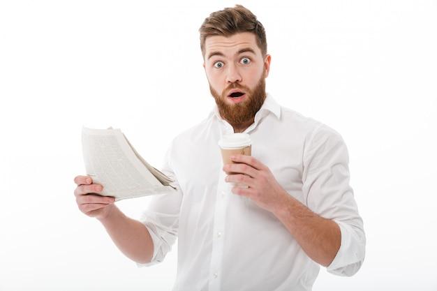 Homem barbudo chocado em roupas de negócios, segurando o jornal Foto gratuita