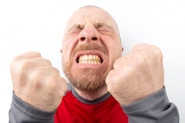 Homem barbudo com emoções fortes e com os punhos cerrados, closeup no branco Foto Premium