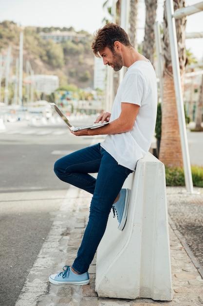 Homem barbudo com jeans segurando um caderno Foto gratuita