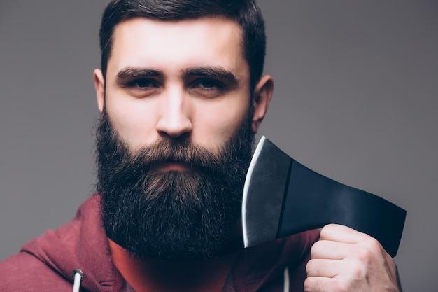 Homem barbudo com machado. corte o cabelo com machado. cabeleireiro masculino ou barbearia. açougueiro brutal em camisa. lenhador pronto para trabalhar na floresta. brutalidade confiante do lenhador. lenhador usa machado. Foto gratuita