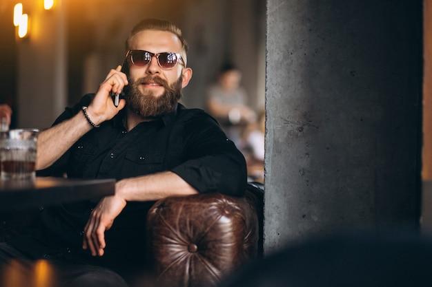Homem barbudo com telefone sentado em um café Foto gratuita