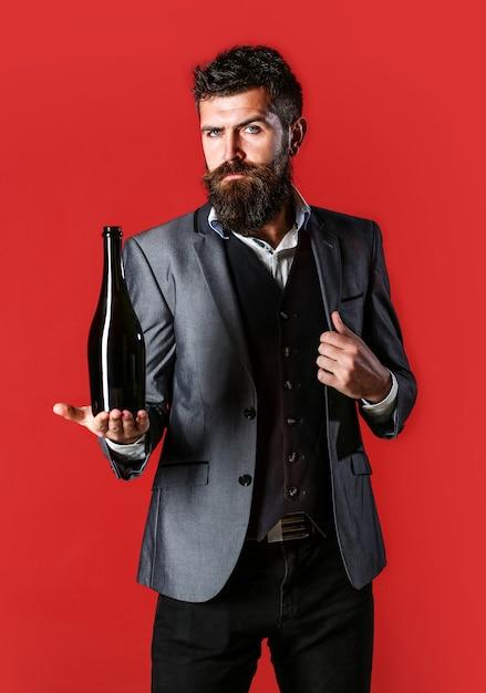 Homem barbudo com uma garrafa de champanhe e uma taça. homem elegante em smoking, terno, jaqueta. homem segurando a garrafa com champanhe, vinho. a pessoa segura uma garrafa de vinho tinto na mão. Foto Premium