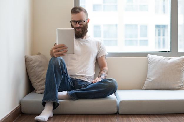Homem barbudo concentrado sentado no travesseiro e usando o tablet Foto gratuita