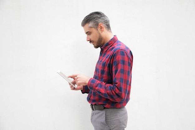 Homem barbudo concentrado usando tablet digital Foto gratuita