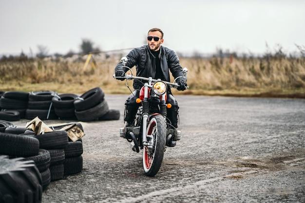 Homem barbudo de óculos escuros e jaqueta de couro, sentado em uma motocicleta vermelha e olhando para a estrada. Foto Premium