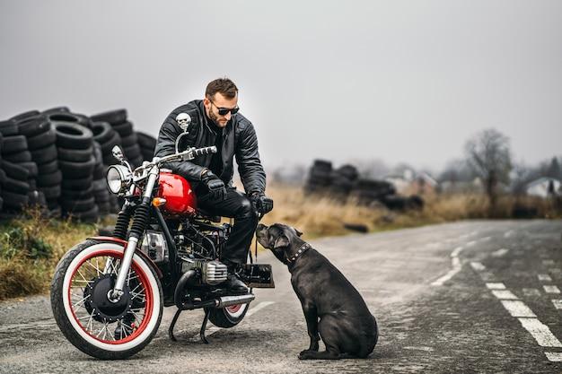 Homem barbudo de óculos escuros e jaqueta de couro, sorrindo enquanto está sentado em uma motocicleta vermelha na estrada com seu cachorro. Foto Premium