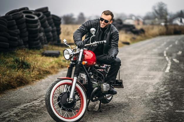 Homem barbudo de óculos escuros e jaqueta de couro, sorrindo enquanto está sentado em uma motocicleta vermelha na estrada. Foto Premium