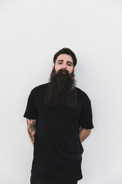 Homem barbudo de pé contra o pano de fundo branco Foto gratuita