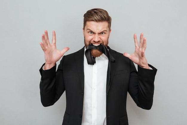 Homem barbudo de terno posando em fundo cinza com gravata Foto gratuita
