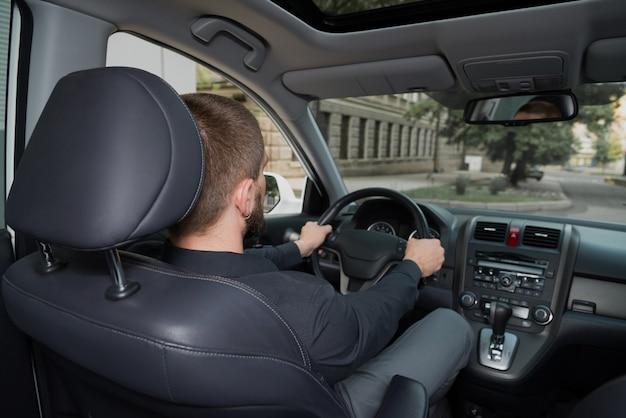 Homem barbudo dirigindo um auto. Foto Premium