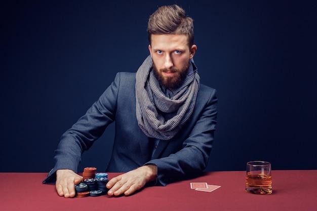 Homem barbudo elegante de terno e lenço jogando no cassino escuro Foto Premium
