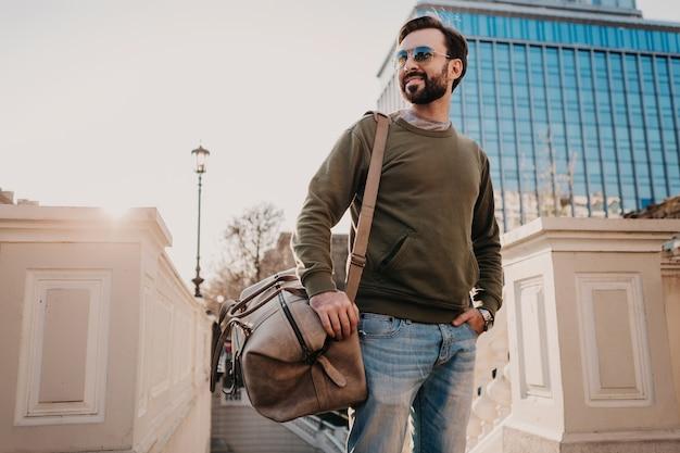Homem barbudo elegante e bonito andando na rua da cidade com uma bolsa de viagem de couro vestindo moletom e óculos escuros, tendência de estilo urbano, dia de sol, confiante e sorridente Foto gratuita