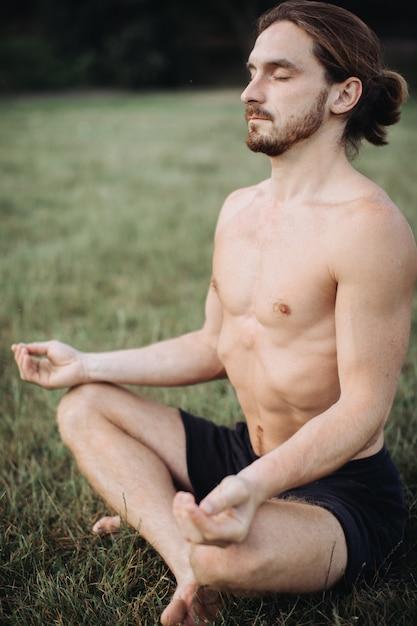 Homem barbudo em pose de lótus, sentado na grama verde, conceito de calma e meditação Foto Premium
