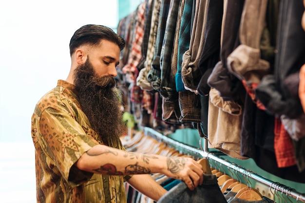 Homem barbudo, escolhendo a camisa pendurada no trilho da loja Foto gratuita