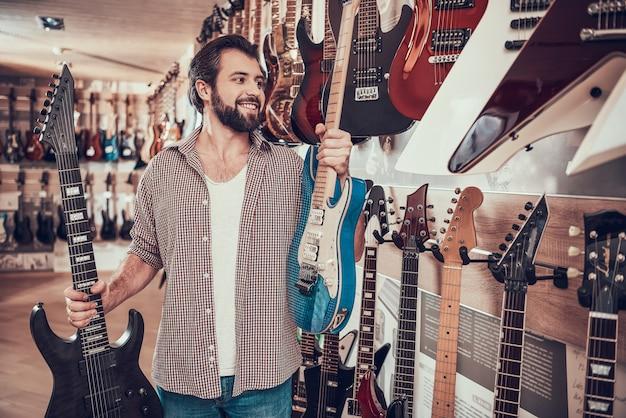Homem barbudo faz escolha entre duas guitarras elétricas Foto Premium
