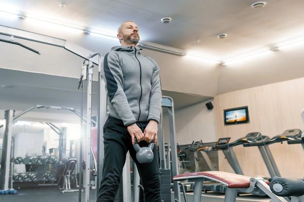 Homem barbudo fazendo exercícios físicos na academia Foto Premium