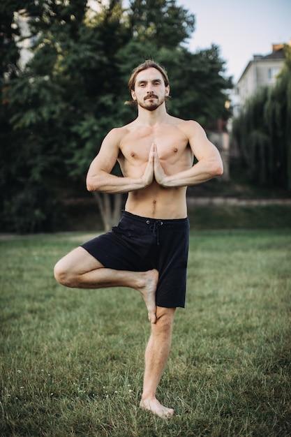 Homem barbudo fazendo yoga no parque verde Foto Premium