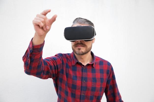Homem barbudo focado no fone de ouvido da realidade virtual Foto gratuita