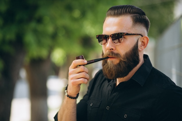 Homem barbudo fumando cachimbo Foto gratuita