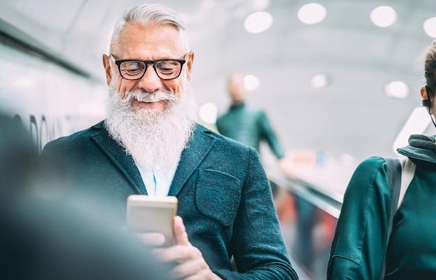 Homem barbudo hipster usando telefone celular inteligente em elevadores de shopping Foto Premium
