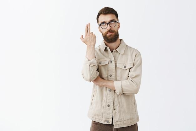 Homem barbudo irritado com óculos posando contra a parede branca Foto gratuita