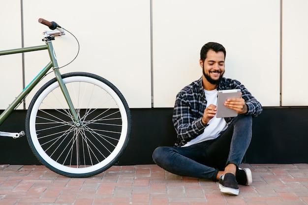Homem barbudo jovem elegante usando um tablet, sorrindo alegremente, assistindo ou lendo algo Foto gratuita