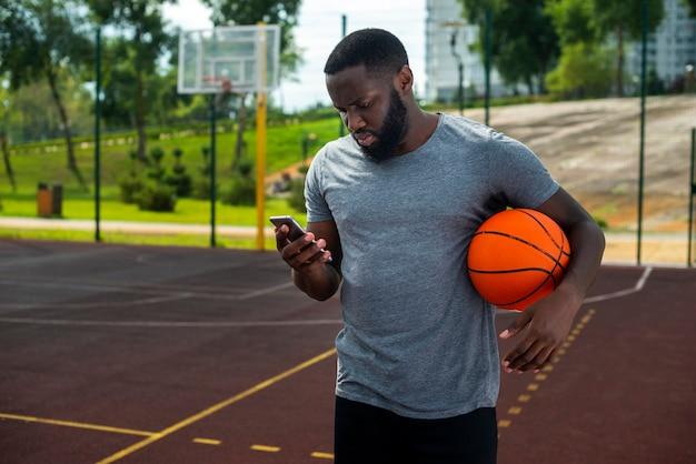 Homem barbudo olhando no telefone plano médio Foto gratuita
