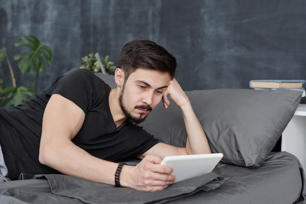 Homem barbudo preguiçoso deitado na cama usando o tablet enquanto perde tempo durante a quarentena Foto Premium