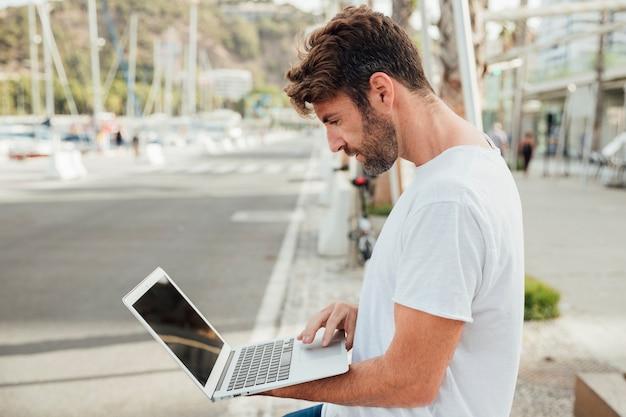 Homem barbudo segurando laptop ao ar livre Foto gratuita