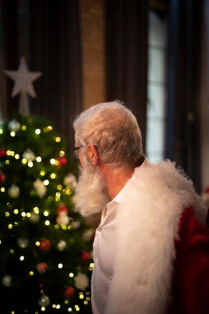 Homem barbudo sênior, olhando para a árvore de natal Foto gratuita