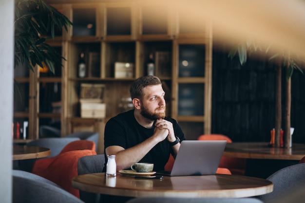 Homem barbudo sentado em um café, bebendo café e trabalhando em um computador Foto gratuita