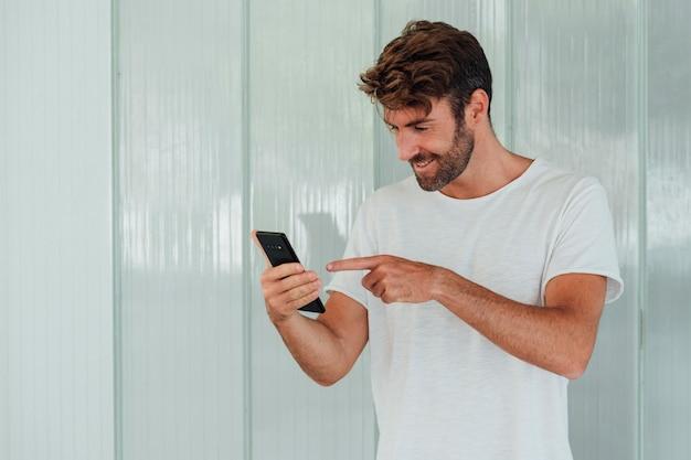 Homem barbudo sorridente apontando para celular Foto gratuita