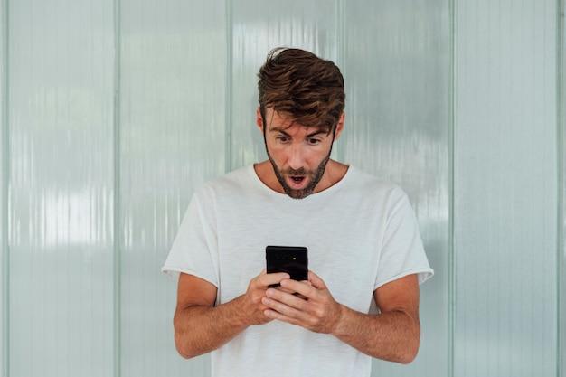 Homem barbudo surpreso com smartphone Foto gratuita