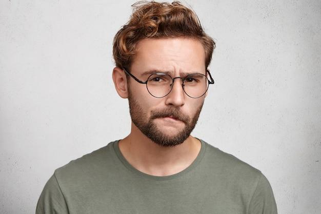 Homem barbudo suspeito olha em dúvida, curva os lábios, fica indeciso, faz careta Foto gratuita