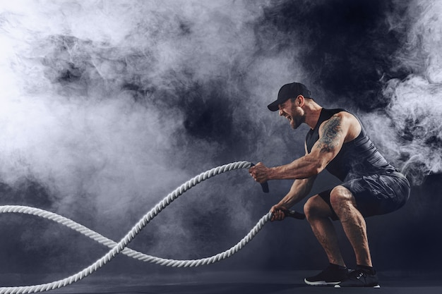 Homem barbudo tatuado musculoso se exercitando Foto Premium