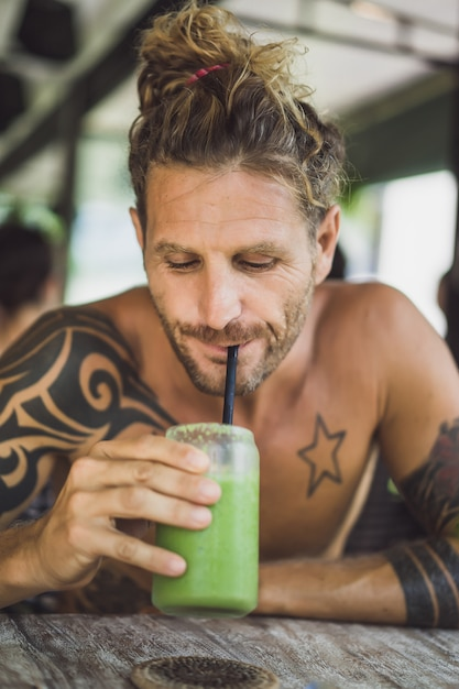 Homem bebe smoothies saudáveis Foto gratuita