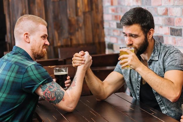 Homem, bebendo, cerveja, enquanto, braço wrestling, com, seu, amigo Foto gratuita