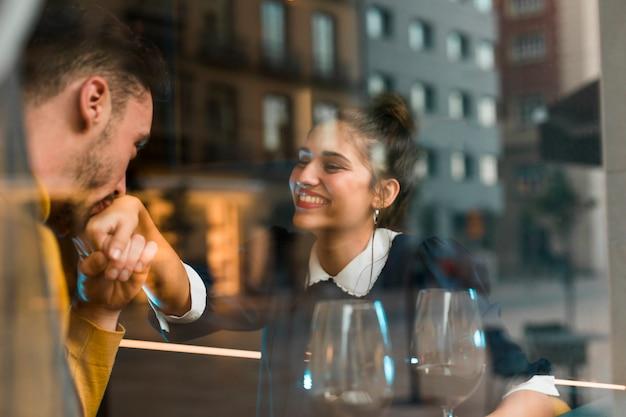 Homem, beijando, mão, de, mulher sorridente, perto, copos vinho, em, restaurante, perto, janela Foto gratuita