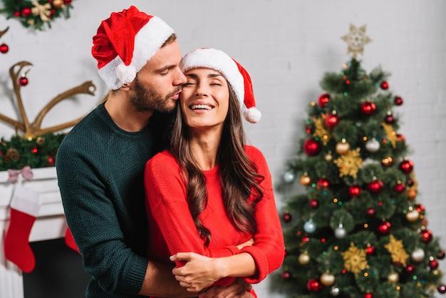 Homem, beijando, mulher feliz, em, natal, chapéu Foto gratuita