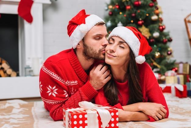 Homem, beijando, mulher, perto, árvore natal Foto gratuita