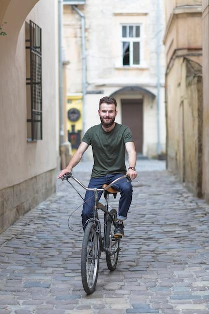 Homem, bicicleta equitação, ligado, godo, apedrejado, rua Foto gratuita